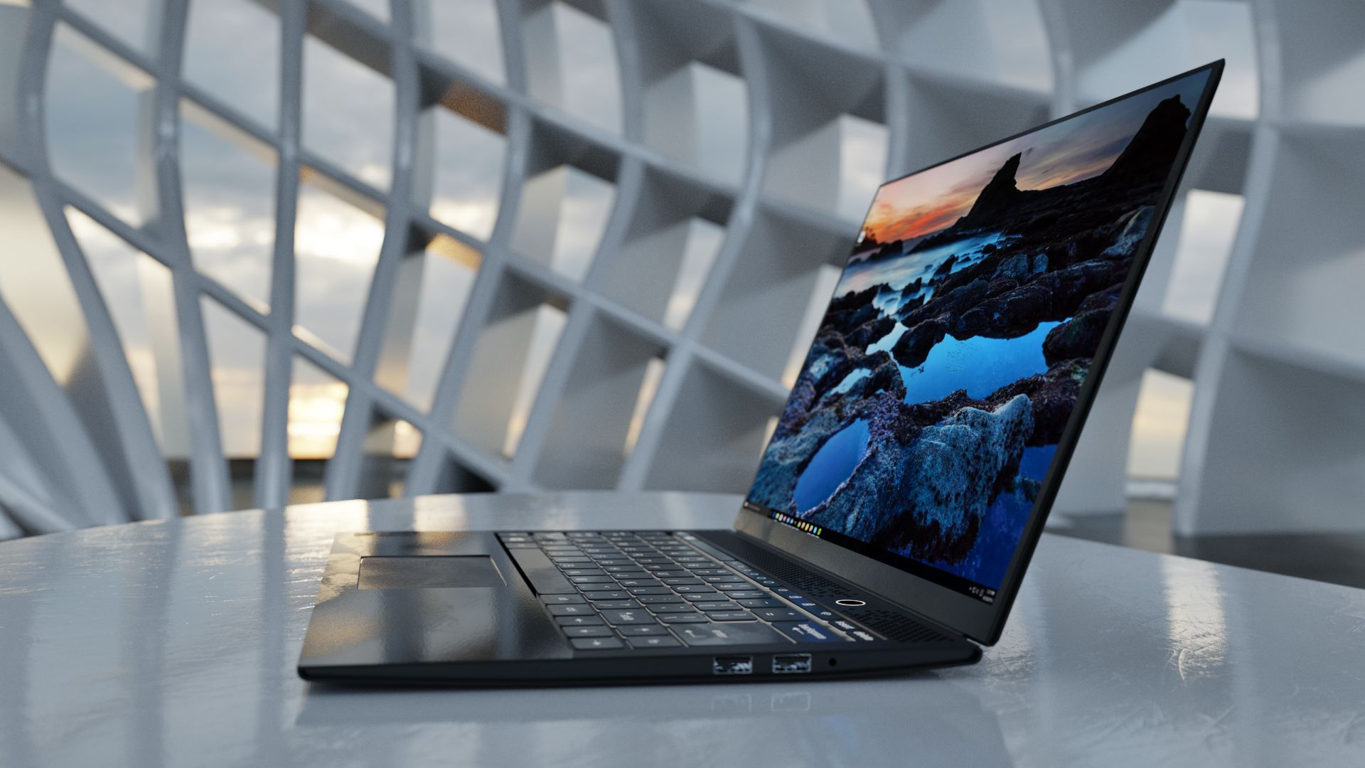 laptop sitting on a desk in an open room with a modern architectural design with sunlight shining through the windows